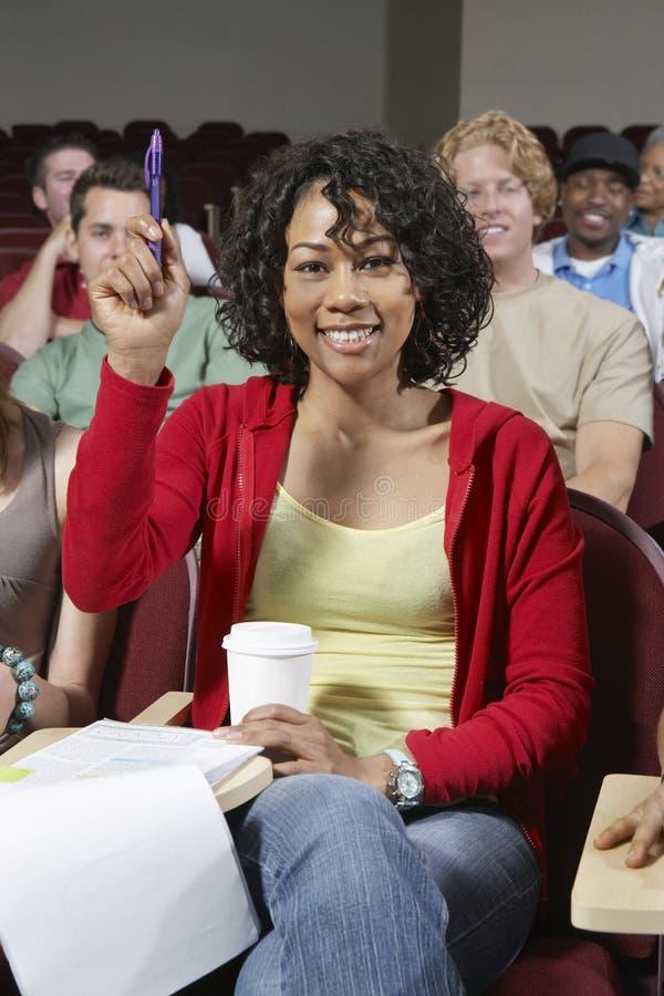 Vrouwelijke Student Answering In Class stock fotografie