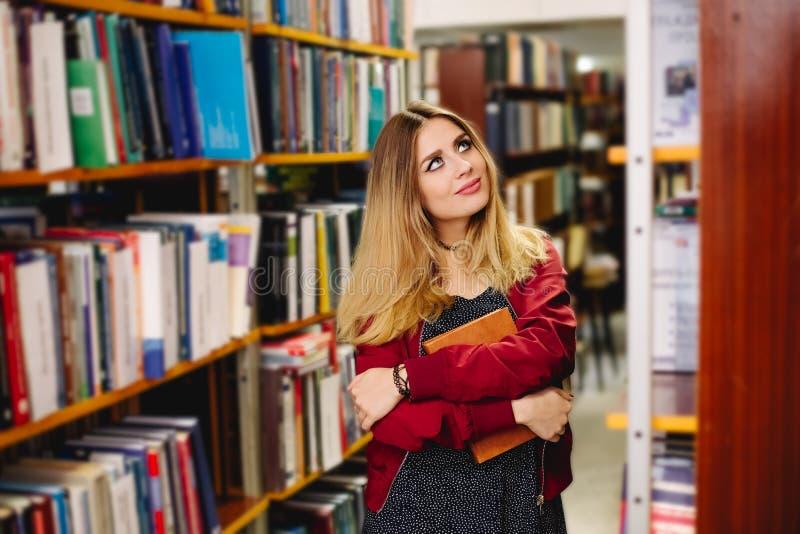 Vrouwelijke student choses een boek in universiteitsbibliotheek Het concept van het onderwijs royalty-vrije stock afbeeldingen