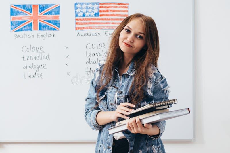 Vrouwelijke student die camera bekijkt Engelstalige school stock fotografie