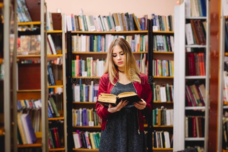 Vrouwelijke student die een boek tussen boekenrekken in universitaire bibliotheek lezen royalty-vrije stock fotografie