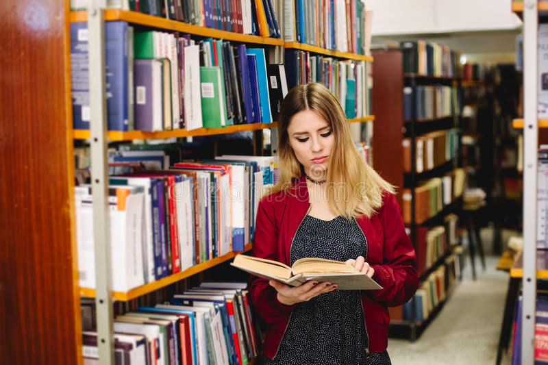 Vrouwelijke student die een boek tussen boekenrekken in universitaire bibliotheek lezen stock afbeeldingen