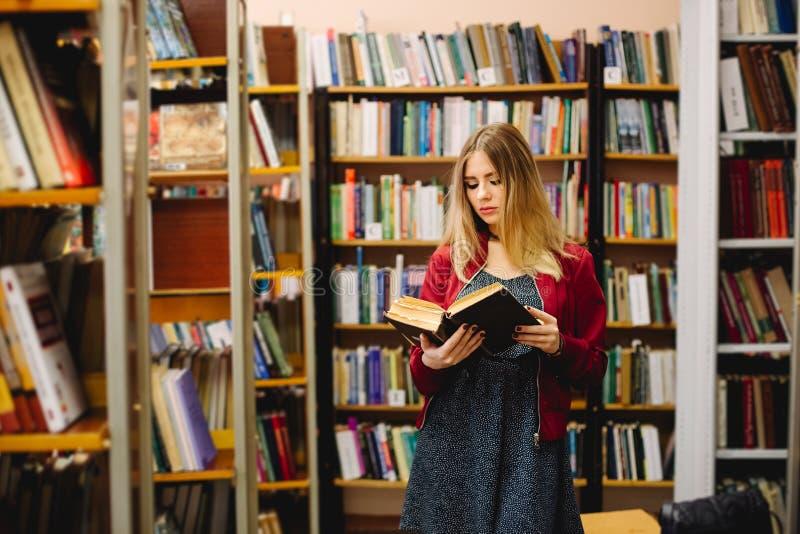 Vrouwelijke student die een boek tussen boekenrekken in universitaire bibliotheek lezen stock fotografie