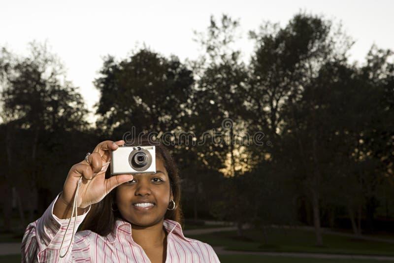 Vrouwelijke student die een foto in openlucht nemen stock foto