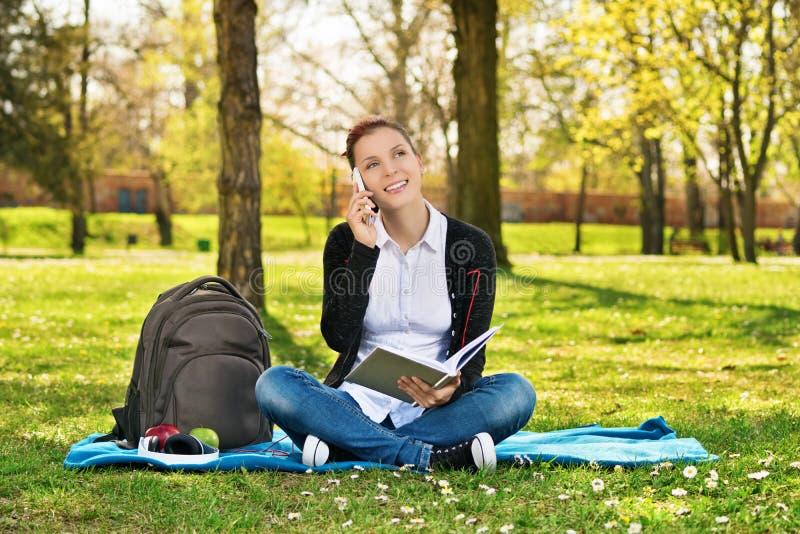 Vrouwelijke student die in een park spreken die op de telefoon spreken stock foto