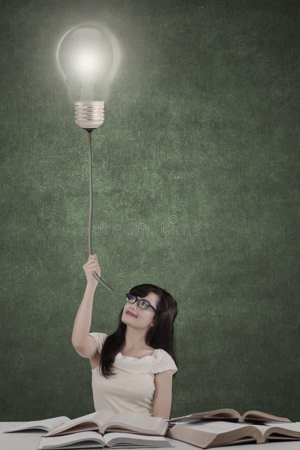 Vrouwelijke student die heldere lamp trekken stock fotografie