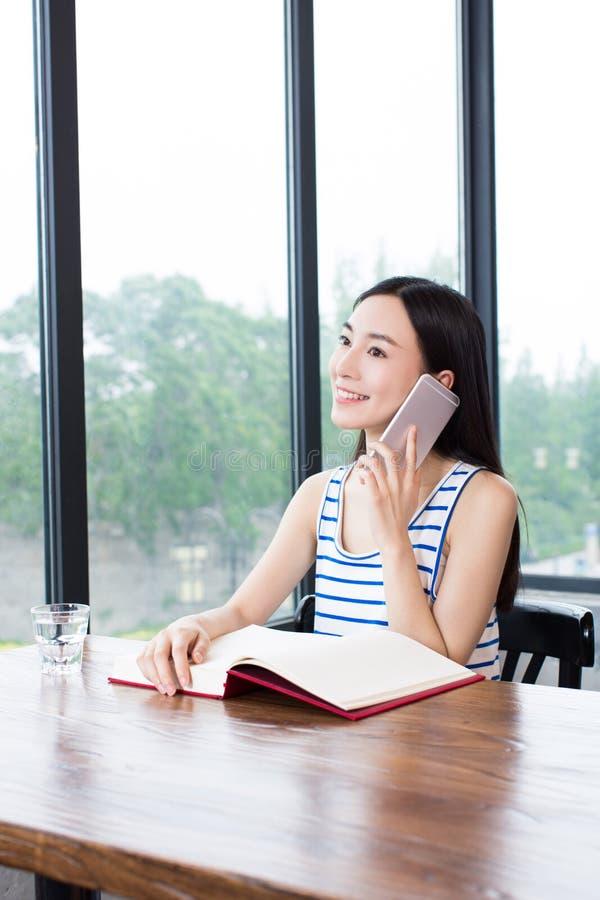Vrouwelijke student die met handboeken en koffie bestuderen royalty-vrije stock afbeeldingen