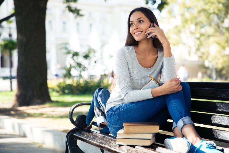 Vrouwelijke student die op de telefoon in openlucht spreken stock afbeeldingen