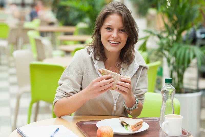 Vrouwelijke student die sandwich in de cafetaria eten stock fotografie