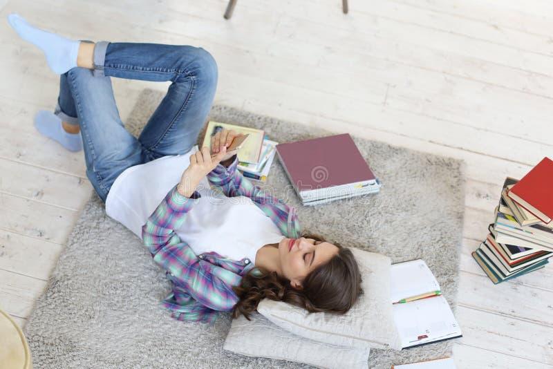 Vrouwelijke student die sociale media controleren alvorens te bestuderen terug te keren, die op vloer tegen comfortabel binnenlan stock afbeeldingen