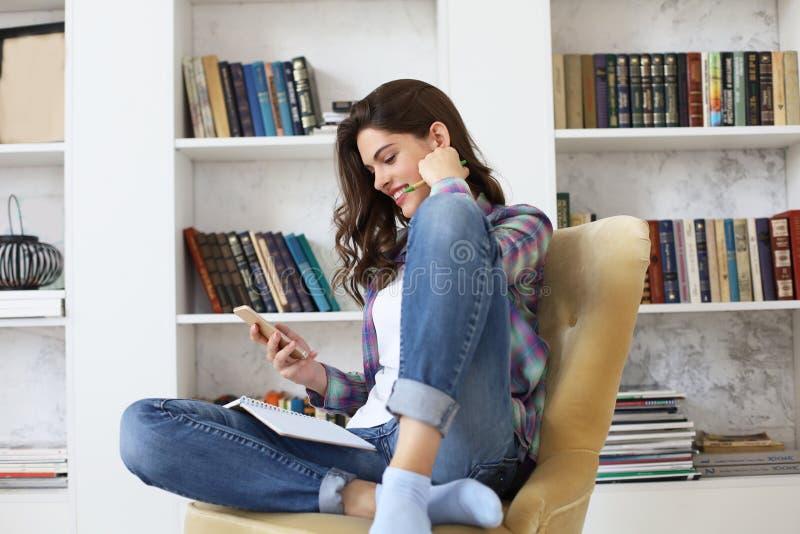 Vrouwelijke student die sociale media controleren alvorens te bestuderen terug te keren, die op vloer tegen comfortabel binnenlan royalty-vrije stock foto's