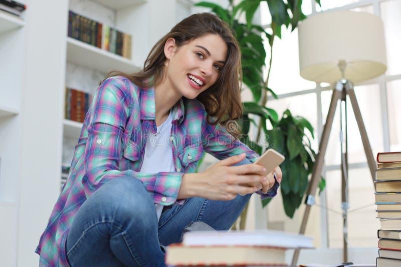 Vrouwelijke student die sociale media controleren alvorens te bestuderen terug te keren, die op vloer tegen comfortabel binnenlan royalty-vrije stock afbeeldingen