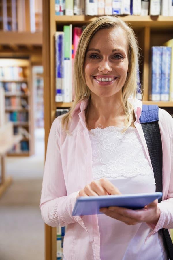 Vrouwelijke student die tablet in bibliotheek gebruiken stock foto's