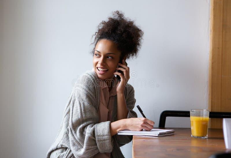 Vrouwelijke student die thuis en op mobiele telefoon spreken werken stock afbeelding