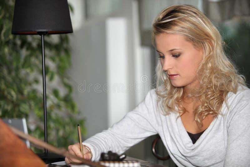 Vrouwelijke student die thuiswerk doen royalty-vrije stock afbeelding