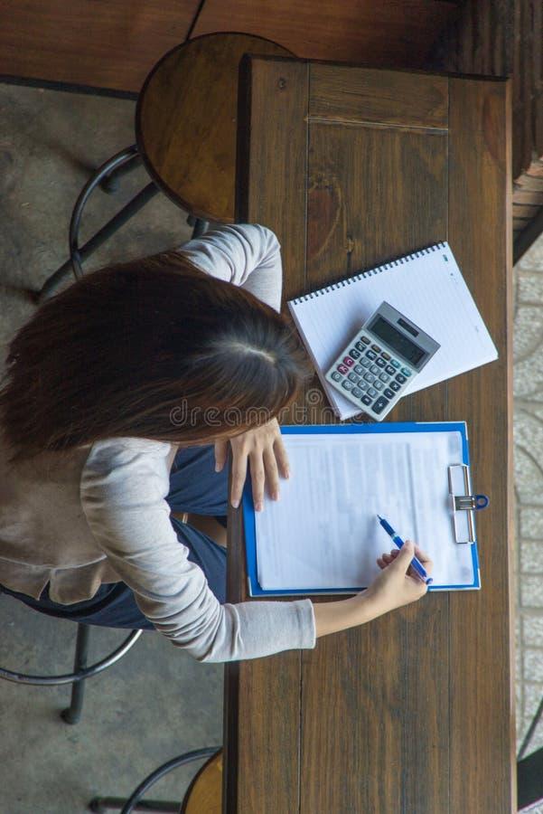 Vrouwelijke student die thuiswerk doen bij bibliotheek stock afbeelding