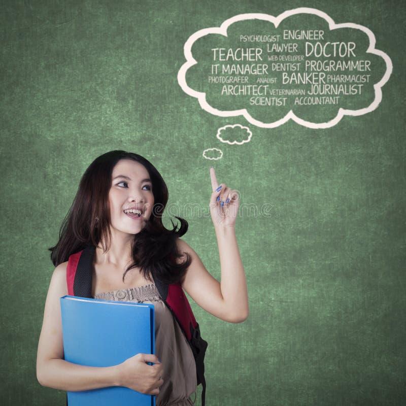 Vrouwelijke student die toekomstige banen in klasse denken stock afbeelding