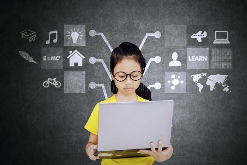 Vrouwelijke student die tot Internet in klaslokaal toegang hebben stock foto