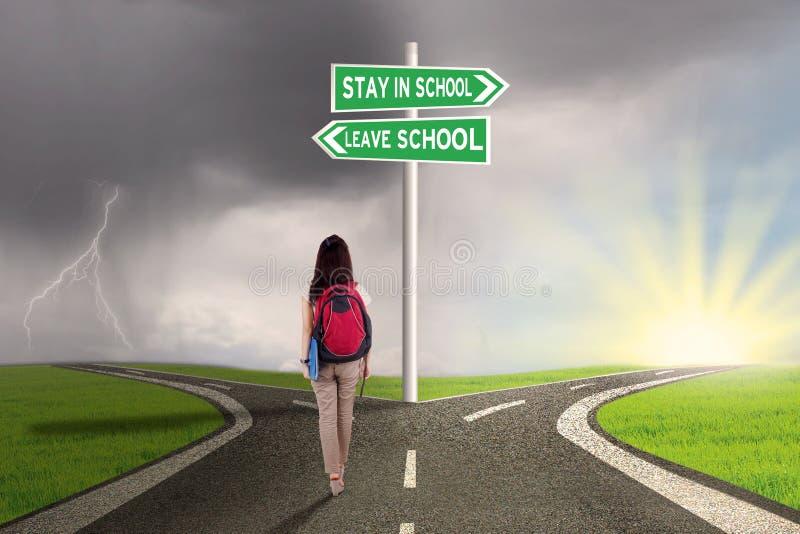 Vrouwelijke student met keuzen om te blijven of school te verlaten stock afbeeldingen