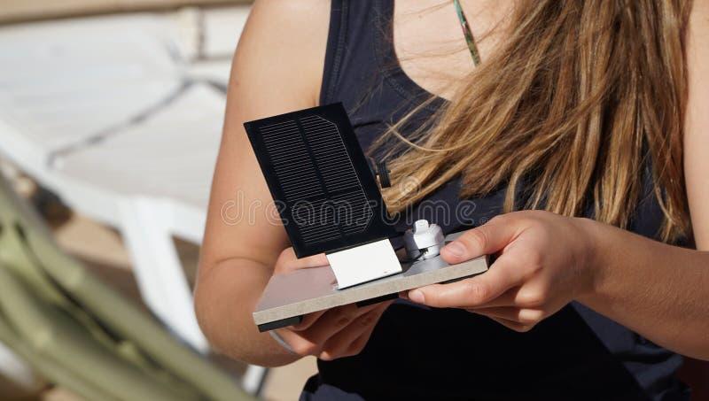 Vrouwelijke student met zonnecelpaneel ter beschikking bij buitenkant royalty-vrije stock afbeelding