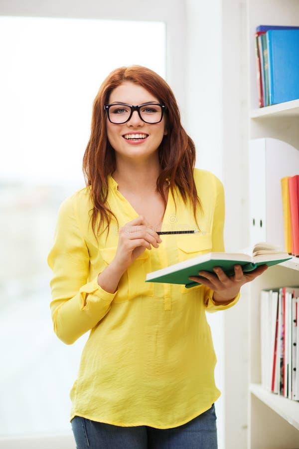 Vrouwelijke student in oogglazen met boek en potlood stock afbeelding