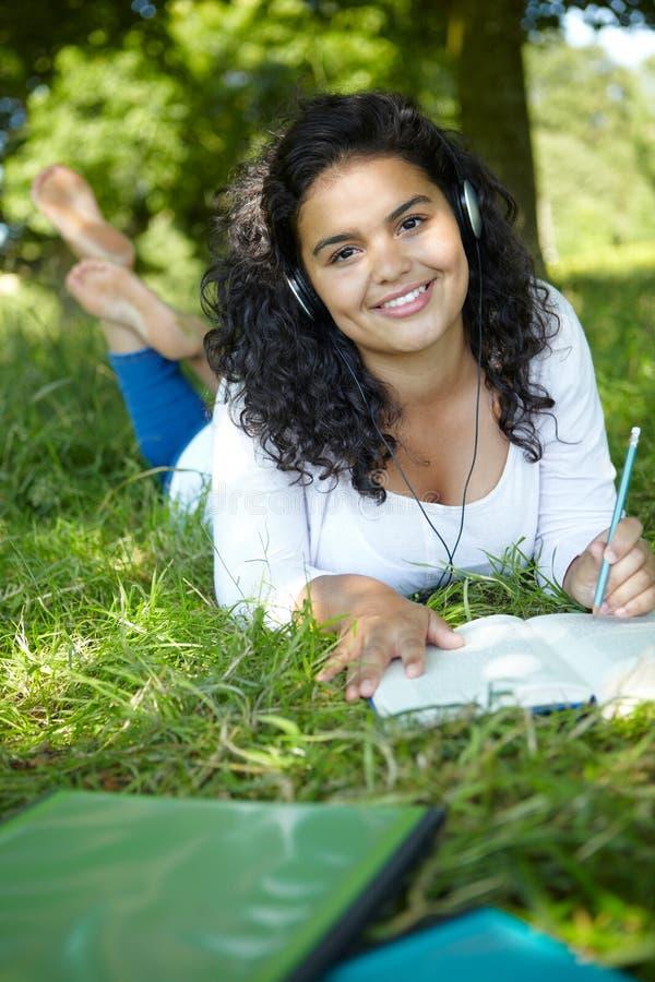 Vrouwelijke Student Revising And Listening aan Muziek in Park royalty-vrije stock foto's