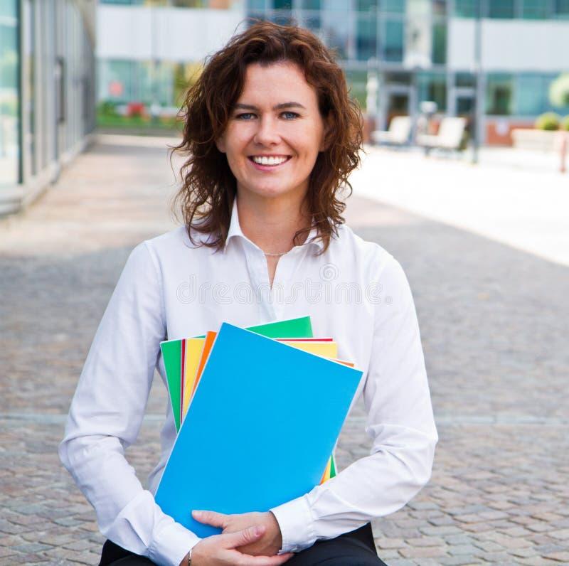 Vrouwelijke studenten met gekleurd notitieboekje stock foto's