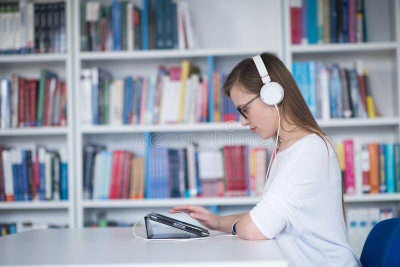 Vrouwelijke studentenstudie in bibliotheek, gebruikend tablet en zoekend voor royalty-vrije stock foto's
