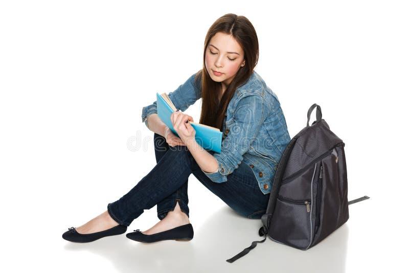 Vrouwelijke studentenzitting op vloer met rugzak die een boek lezen stock foto's