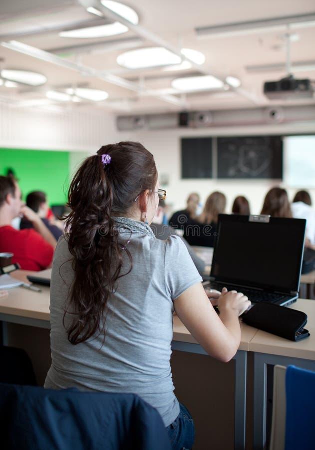 Vrouwelijke studentzitting in een klaslokaal stock afbeeldingen