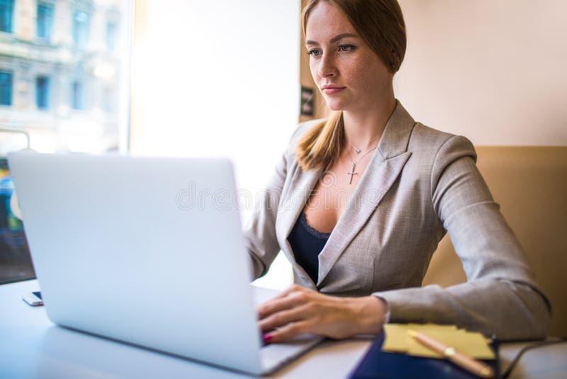 Vrouwelijke succesvolle tevreden manager die afstandsbaan via netbook hebben Videoconferentie stock foto