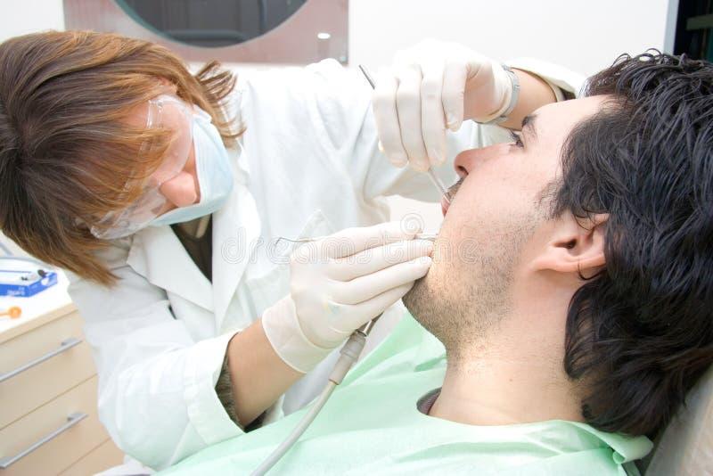 Vrouwelijke tandarts die een patiënt onderzoekt royalty-vrije stock fotografie