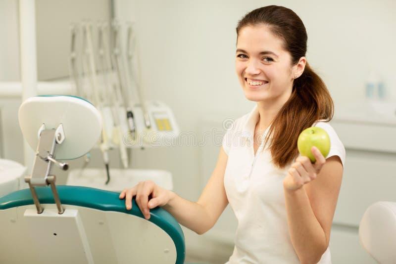Vrouwelijke tandarts die en een groene appel, een tandzorg en een preventieconcept glimlachen houden stock afbeeldingen