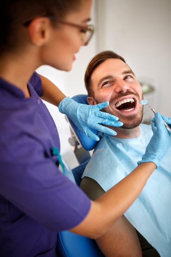 Vrouwelijke tandarts die met tandspiegel patient's tanden kijken stock foto