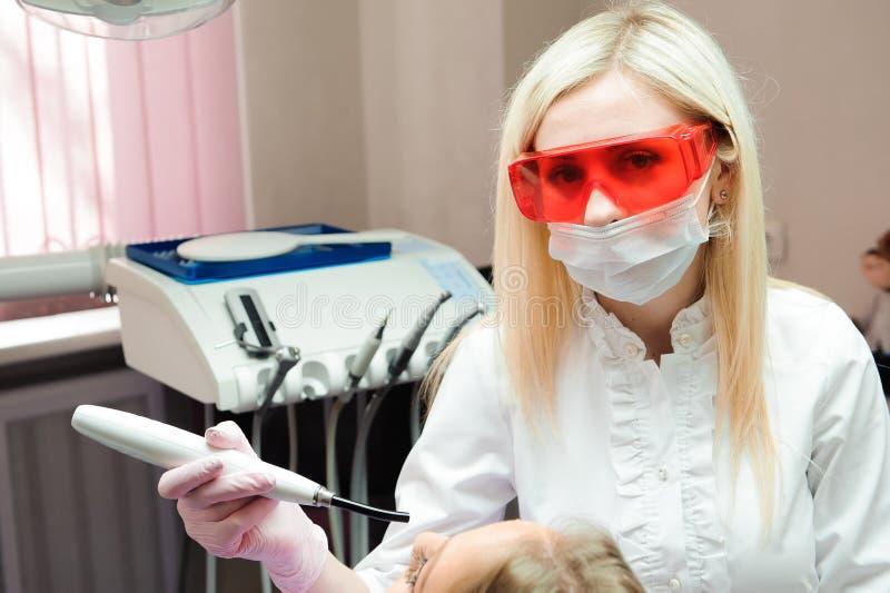 Vrouwelijke tandarts die tanden in tandbureau onderzoeken stock fotografie