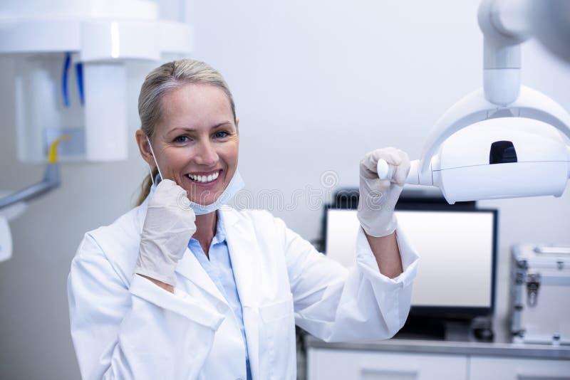 Vrouwelijke tandarts die tandlichten houden stock foto