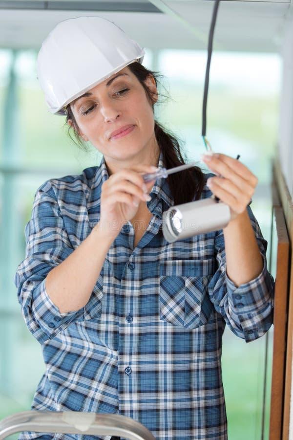 Vrouwelijke technicus die kabeltelevisie-camera aanpassen stock afbeeldingen