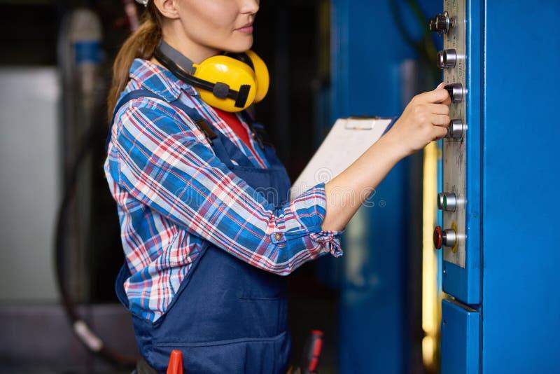 Vrouwelijke Technicus Operating Machines bij Fabriek stock foto's