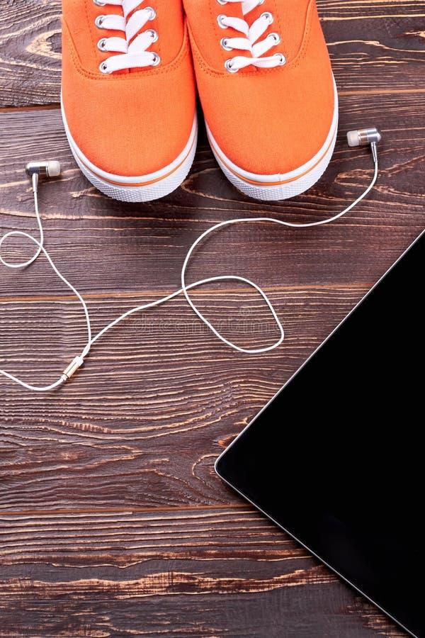 Vrouwelijke tennisschoenen, oortelefoons en PC-tablet stock foto