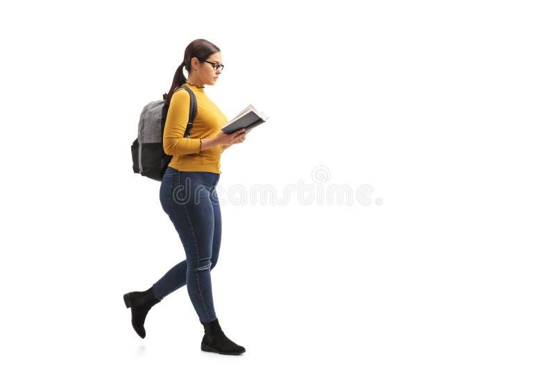 Vrouwelijke tienerstudent die een boek en het lopen lezen stock foto