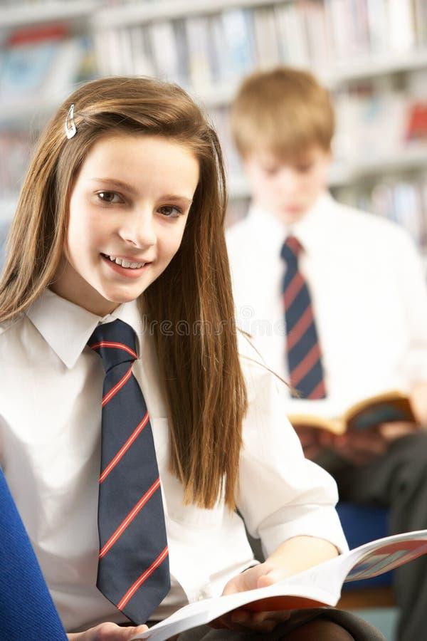 Vrouwelijke TienerStudent in het Boek van de Lezing van de Bibliotheek royalty-vrije stock fotografie