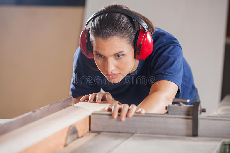 Vrouwelijke Timmerman Cutting Wood With Tablesaw stock foto