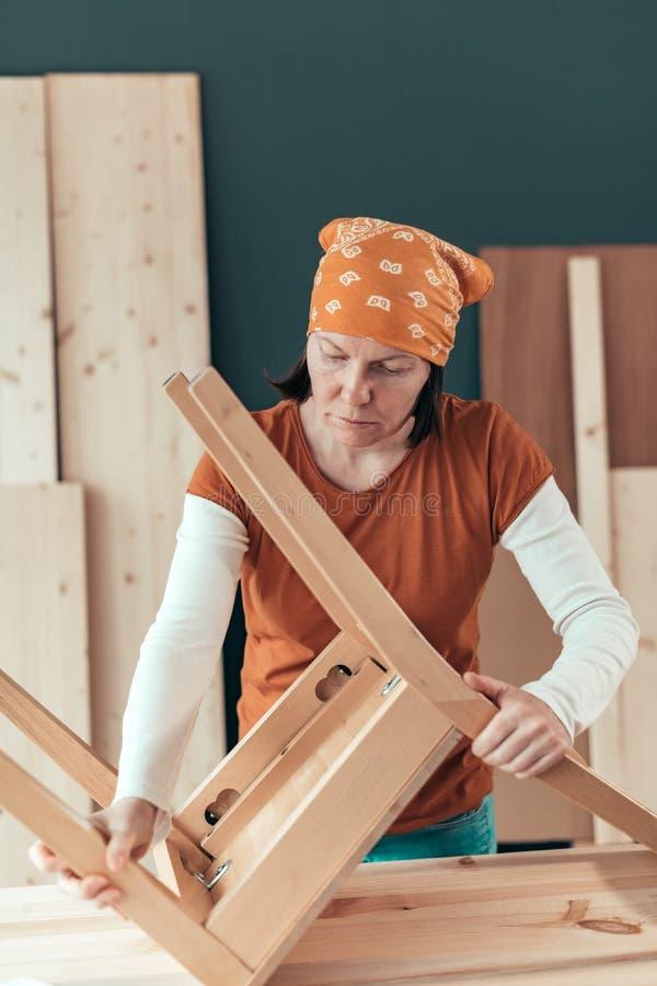 Vrouwelijke timmerman die houten stoelzetel in workshop herstellen royalty-vrije stock foto