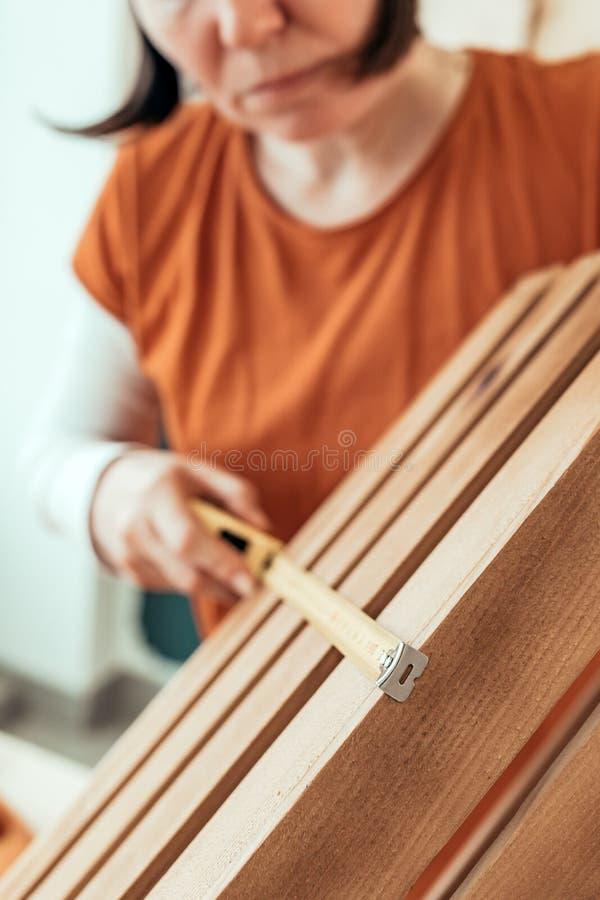 Vrouwelijke timmermansband die houten krat meten stock foto