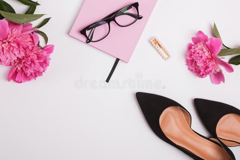 Vrouwelijke toebehoren en mooie roze pioenen op de witte achtergrond royalty-vrije stock afbeeldingen