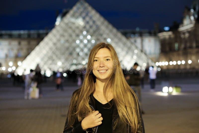 Vrouwelijke toerist in de piramide van het Louvreglas op achtergrond, Parijs stock foto
