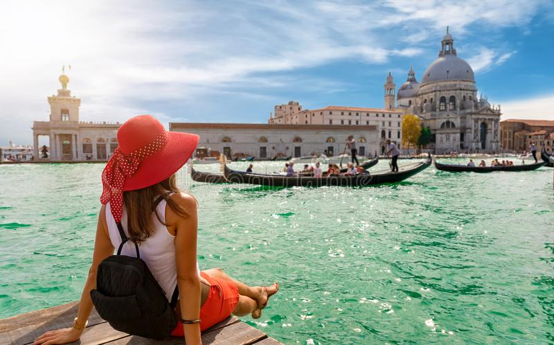 Vrouwelijke toerist die Basiliekdi Santa Maria della Salute en Canale Grande in Venetië, Italië kijken stock foto