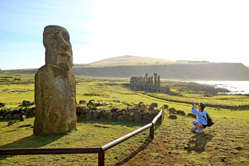 Vrouwelijke toerist die foto van solitaire Moai nemen dichtbij beroemde 15 Moais op het platform van Ahu Tongariki, Pasen-Eiland royalty-vrije stock foto's