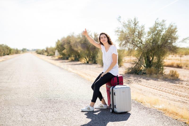 Vrouwelijke toerist die langs een weg liften royalty-vrije stock fotografie