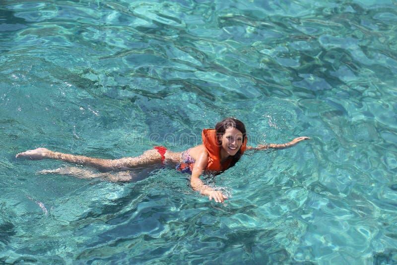 Vrouwelijke toerist die leren te zwemmen gebruikend een reddingsvest stock afbeeldingen