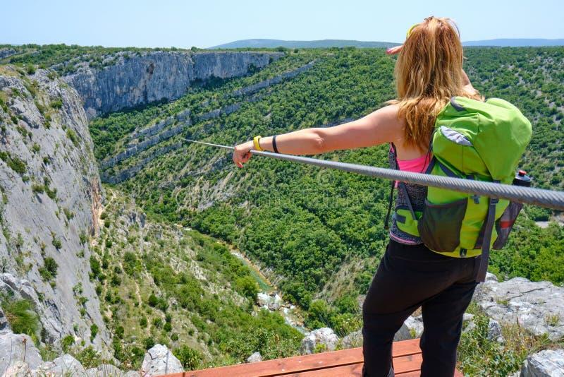 Vrouwelijke toerist die zipline boven Cikola-canion, in Kroatië bekijken, terwijl status op het beginnende houten platform royalty-vrije stock foto's